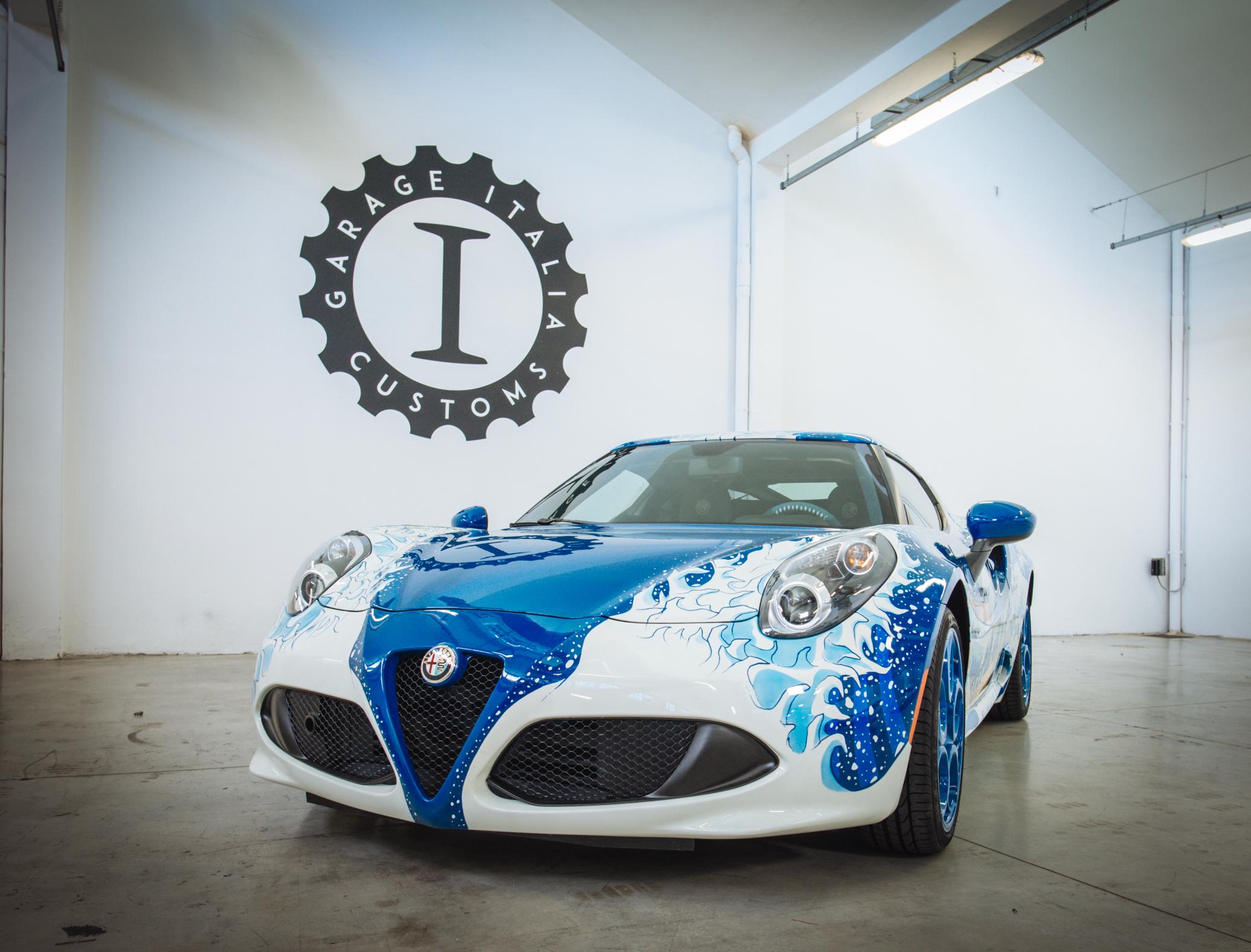 """Garage Italia Customs ha presentato l'Alfa Romeo 4C Hokusai che sarà alla mostra Piston Head II: Artists Engage The Automobile nella galleria Venus di Los Angeles. La 4C Hokusai vuole essere la celebrazione dell'incontro tra la cultura giapponese e quella italiana. La sportiva Alfa Romeo è stata scelta perché è un simbolo dell'italianità amata dai giapponesi, che da sempre sono grandi appassionati del marchio di Arese. Sulla sua carrozzeria è stata aerografata a mano l'opera giapponese più conosciuta al mondo, """"La Grande Onda"""" del Maestro Katsushika Hokusai. Un'immagine che rimanda subito alla grandezza e alla forza della natura, in contrapposizione alla fragilità dell'uomo rappresentata dalle barche dei pescatori. L'onda domina tutta la parte posteriore della fiancata e l'intera superficie del tetto, seguendo sinuosamente le forme della quanto mai insolita """"tela"""". La livrea diventa così metafora dell'emozioni che travolgono il guidatore quando si trova al volante di una vettura Alfa Romeo dalle caratteristiche tecniche e dalle prestazioni di altissimo livello come quelle della 4C. Infine la scelta dei materiali per il rivestimento interno, come il denim giapponese Kubaro e la pelle Foglizzo che richiama le squame della carpa, sono un chiaro riferimento al Giappone, così come la particolare lavorazione della corona del volante e della leva del freno a mano che si ispira al Tsukamaki, l'arte di rivestire l'elsa della Katana."""