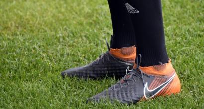 Iran i giocatori comprano gli scarpini in un negozio