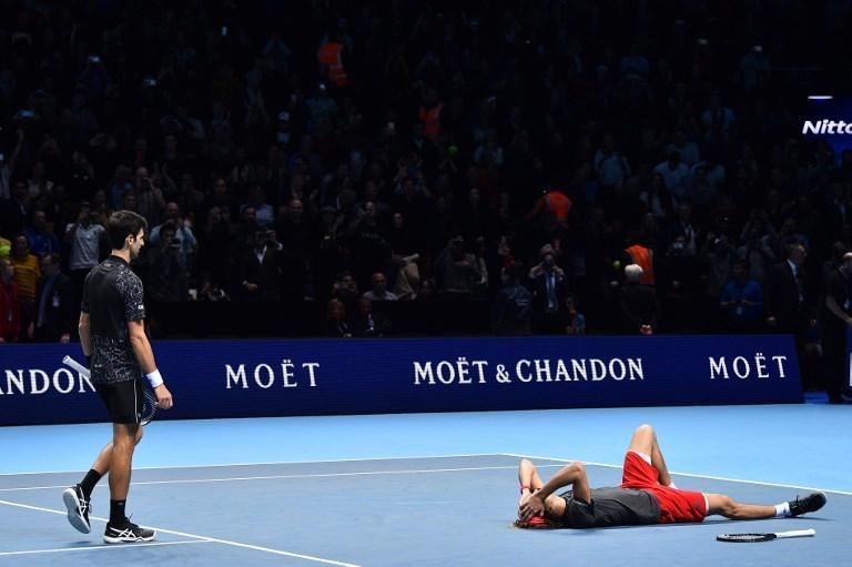 Zverev esulta a terra mentre Djokovic si avvicina per fargli i complimenti nella finale delle ATP Finals (18 novembre)