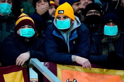 L'emergenza coronavirus arriva anche a Gand, dove i tifosi della Roma nel settore ospiti indossano la mascherina.