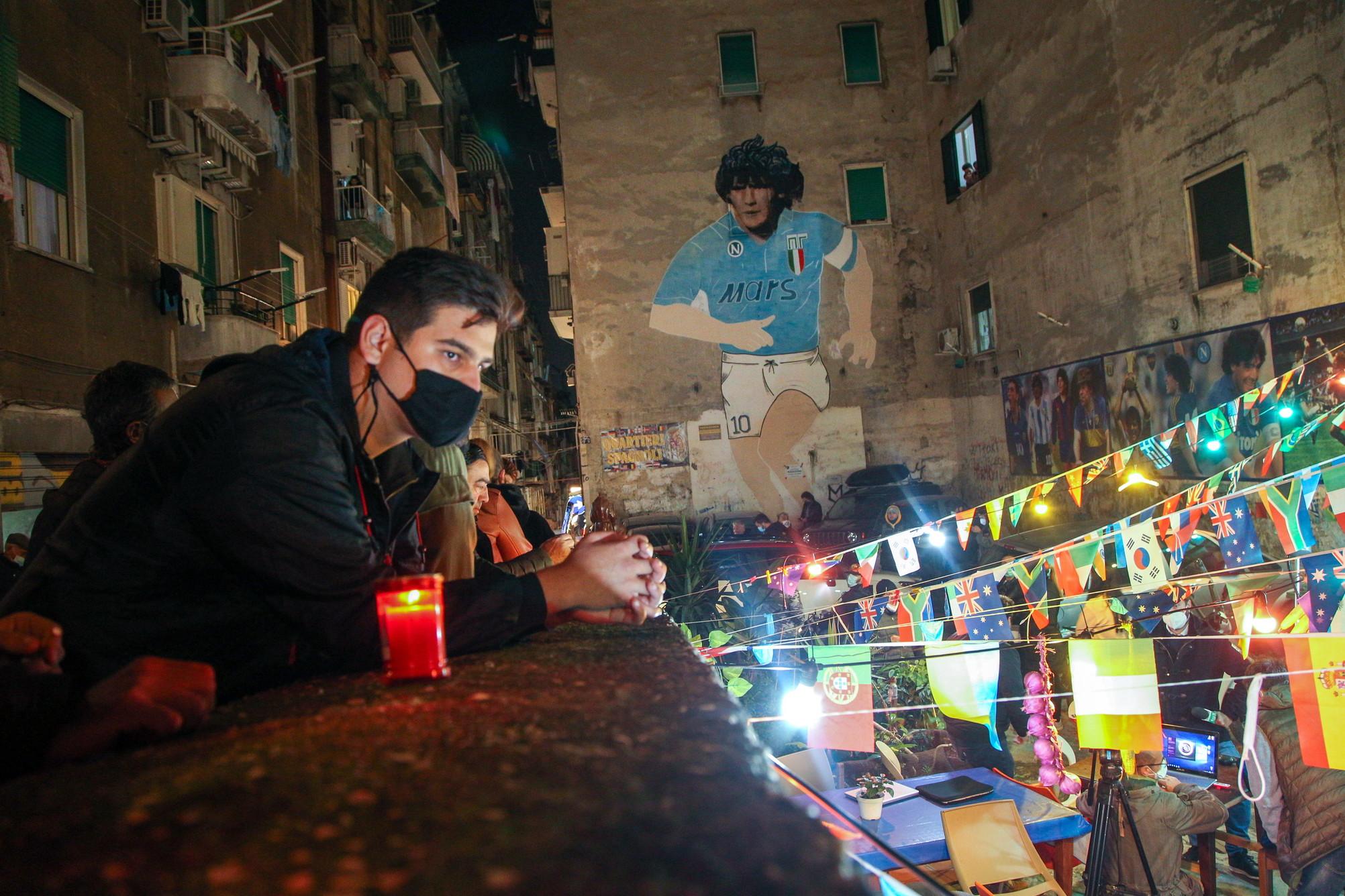 Bengala rossi&nbsp;e il&nbsp;coro &quot;Ho visto Maradona&quot;. Cos&igrave;&nbsp;i tifosi del Napoli hanno fatto partire la commemorazione dell&#39;ex asso argentino che&nbsp;ai Quartieri Spagnoli, nella piazzetta che ospita il murales di Diego. I tifosi sono continuati&nbsp;ad arrivare in una sorte di pellegrinaggio nella piazzetta&nbsp;esprimendo la loro commozione. Una tipografia ha stampato in pochissimo tempo dei manifesti di lutto con un&#39;immagine della Madonna e un pallone e la scritta: &quot;&Egrave;&nbsp;venuto a mancare Diego Armando Maradona. La Napoli che piange. Ciao Dio del calcio&quot;.&nbsp;Centinaia di napoletani si sono raccolti anche davanti allo stadio San Paolo, nell&#39;area dell&#39;ingresso della Curva B, per ricordare insieme Maradona e condividere il dolore per il lutto. I tifosi, nonostante la zona rossa e&nbsp;il coprifuoco per il covid, si sono ritrovati spontaneamente, tutti con le mascherine, portando sciarpe, foto, disegni dei bambini e legandoli alle transenne dello stadio. Davanti ai cancelli sono state accese candele e posati mazzi di fiori.<br /><br />