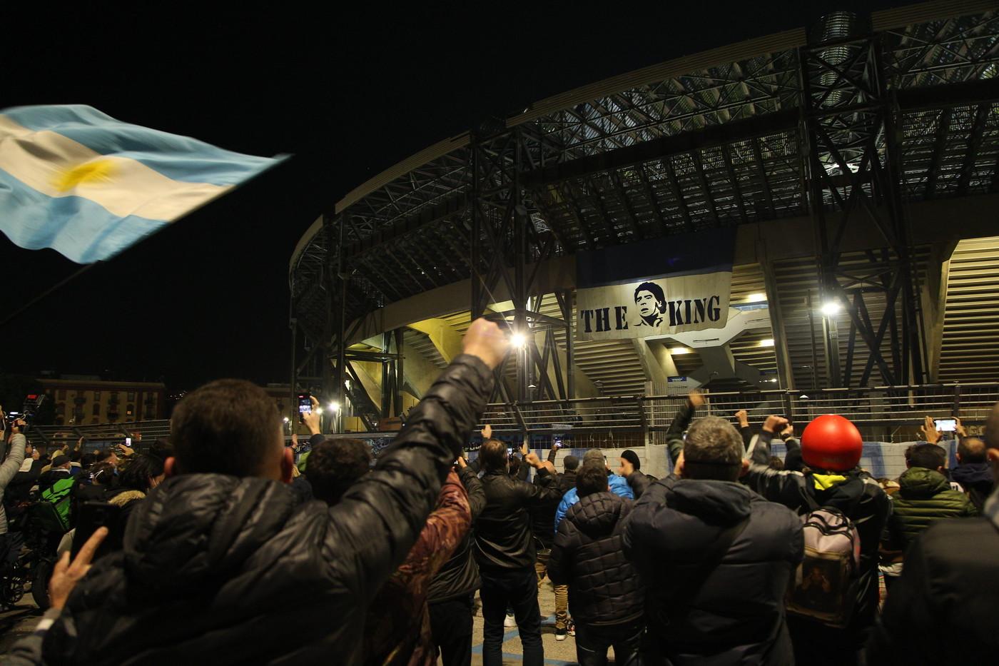 La lunga notte di Napoli per ricordare Diego Armando Maradona ha avuto come fulcro lo stadio San Paolo: diverse centinaia di tifosi si sono riversati davanti all&#39;impianto per una sorta di veglia funebre dai toni toccanti. Un silenzio quasi composto, rotto da qualche coro, tanti striscioni e bandiere, le preghiere di fronte alle foto del Pibe&nbsp;e ai lumini. Nel frattempo, nei quartieri Spagnoli vicino al murales del&nbsp;1987, altre decine di tifosi facevano lo stesso.<br /><br />