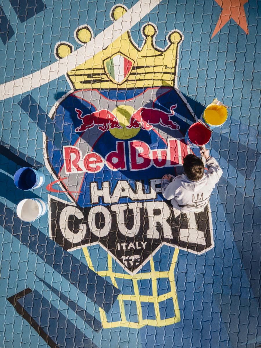 Un gigantesco cestista si staglia sull&#39;intero campo da basket dello Scalo S. Lorenzo a Roma, che viene invaso dai colori. &Egrave; questa la splendida opera d&#39;arte realizzata dal giovane e talentuoso street artist PISKV, che ha dato una nuova veste alla struttura del quartiere. La realizzazione era stata prevista in occasione del Red Bull Half Court, il torneo di basket internazionale 3vs3 in programma a fine ottobre 2020 a Roma, poi rimandato al 2021. Un progetto di riqualificazione e miglioramento dell&#39;impianto, uno dei pi&ugrave;&nbsp;grandi in Europa, che si pone un obiettivo chiaro: realizzare un&#39;opera che potesse vivere ed essere apprezzata in primis da tutto il quartiere, diventando poi anche un punto di riferimento per i tanti appassionati di basket della Capitale. Per questo si &egrave; voluto coinvolgere il giovane Francesco Persichella, in arte PISKV, originario di Canosa di Puglia e romano d&#39;adozione, che ha realizzato l&#39;enorme dipinto, utilizzando materiali di qualit&agrave;&nbsp;e destinati a durare nel tempo. PISKV&nbsp;&egrave;&nbsp;noto per aver donato alla Capitale altre opere straordinarie, come quella all&#39;impianto sportivo municipale Tellene con il murales dedicato a Kobe Bryant, campione NBA cresciuto in Italia, o quelle dedicate alle icone del cinema italiano (Banfi, Verdone, Sordi). &quot;L&#39;idea di questo progetto &egrave; nata dalle linee stesse del contesto urbano. Ho osservato lo spazio dall&#39;alto e ho inserito nelle forme del playground la planimetria del Colosseo, perch&eacute;&nbsp;volevo dargli una forte identit&agrave;&quot;. - Ha commentato PISKV - &quot;Sul Colosseo idealmente si staglia un giocatore di basket nell&#39;atto della schiacciata, l&#39;atto piu&#39; famoso dello Street Basket. Linee dinamiche e una vivacita&#39; dei colori conferiscono forza al disegno, &quot;schiacciando&quot; davvero la realta&#39; grigia che distingueva precedentemente questo campo&quot;.<br /><br />