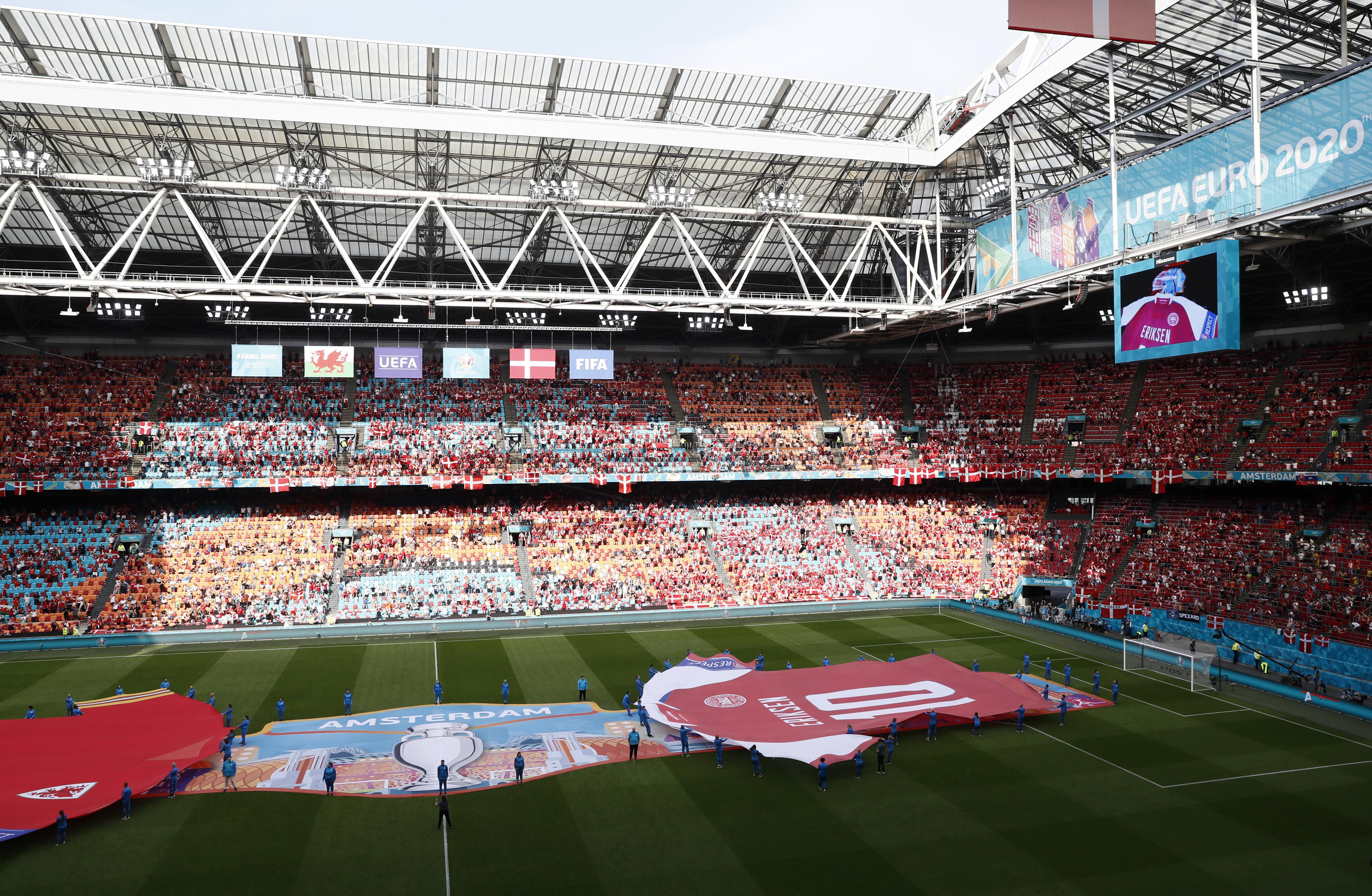 Christian Eriksen non pu&ograve; essere in campo a trascinare la sua Danimarca nello stadio che lo ha visto affermarsi nel calcio che conta con la maglia dell&#39;Ajax, ma il centrocampista dell&rsquo;Inter &egrave; comunque il grande protagonista del prepartita degli ottavi col Galles. Alla Johan Cruijff Arena hanno voluto infatti omaggiarlo portando in campo una maglia gigante della Danimarca con il numero 10. Dopo l&rsquo;omaggio dello stadio quello del Galles: Gareth Bale ha consegnato a Simon Kjaer una maglia del Galles, personalizzata con il nome di Eriksen e l&rsquo;immancabile numero 10.<br /><br />