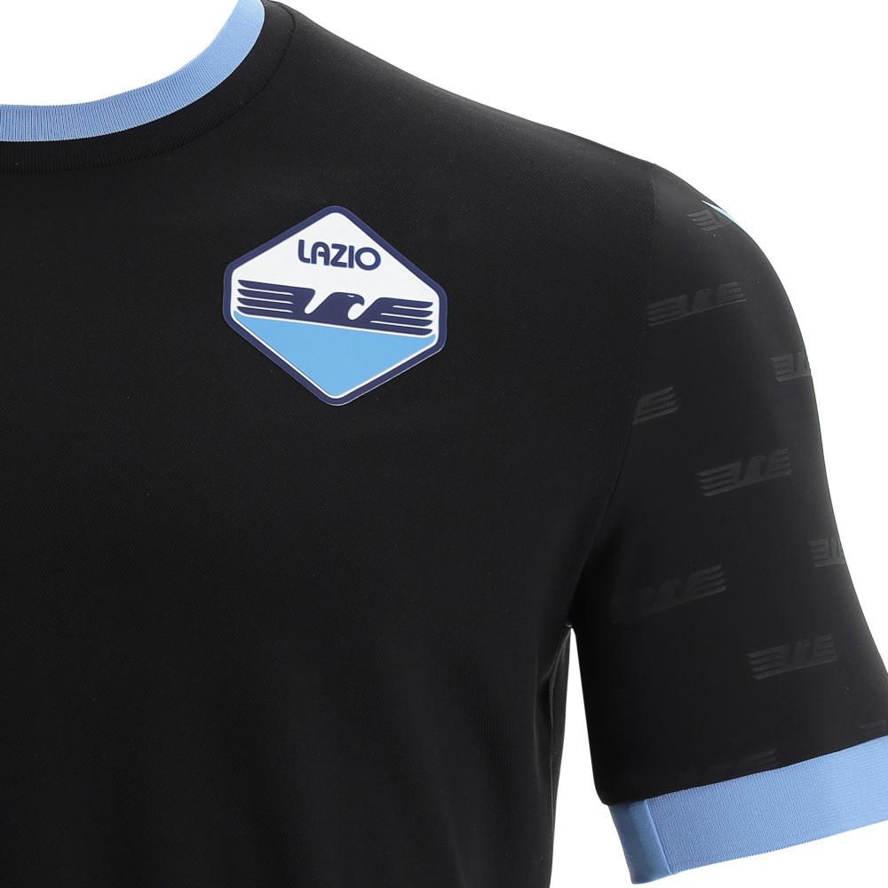 Ad una settimana dalla presentazione della prima maglia della&nbsp;S.S.Lazio&nbsp;per la prossima stagione, il club e&nbsp;Macron, sponsor tecnico dei biancocelesti, hanno svelato la&nbsp;nuova maglia &ldquo;Third&rdquo;&nbsp;per la quale si &egrave; scelto il colore nero arricchito da riferimenti alla grafica della storica &lsquo;maglia bandiera&rdquo;.<br /> <br /> La nuova&nbsp;&ldquo;Third&rdquo;&nbsp;&egrave;&nbsp;total black&nbsp;a girocollo in maglieria con bordi celesti, cos&igrave; come celesti sono i bordi manica. Il dettaglio di design che caratterizza questa maglia &egrave; dato dalla grafica all over, presente sulle maniche, con l&rsquo;aquila stilizzata dell&rsquo;iconica e tanto amata dai tifosi maglia bandiera. Il riferimento alla storica maglia nata nei primi anni &rsquo;80 &egrave; dato anche dalla patch in silicone posta sul petto a sinistra che ripropone il disegno dell&rsquo;aquila con le ali tese ed aperte al posto del tradizionale stemma della S.S.Lazio. Accanto all&rsquo;aquila sul petto, a destra, in stampa siliconica il&nbsp;Macron Hero, logo del brand italiano.<br /><br />