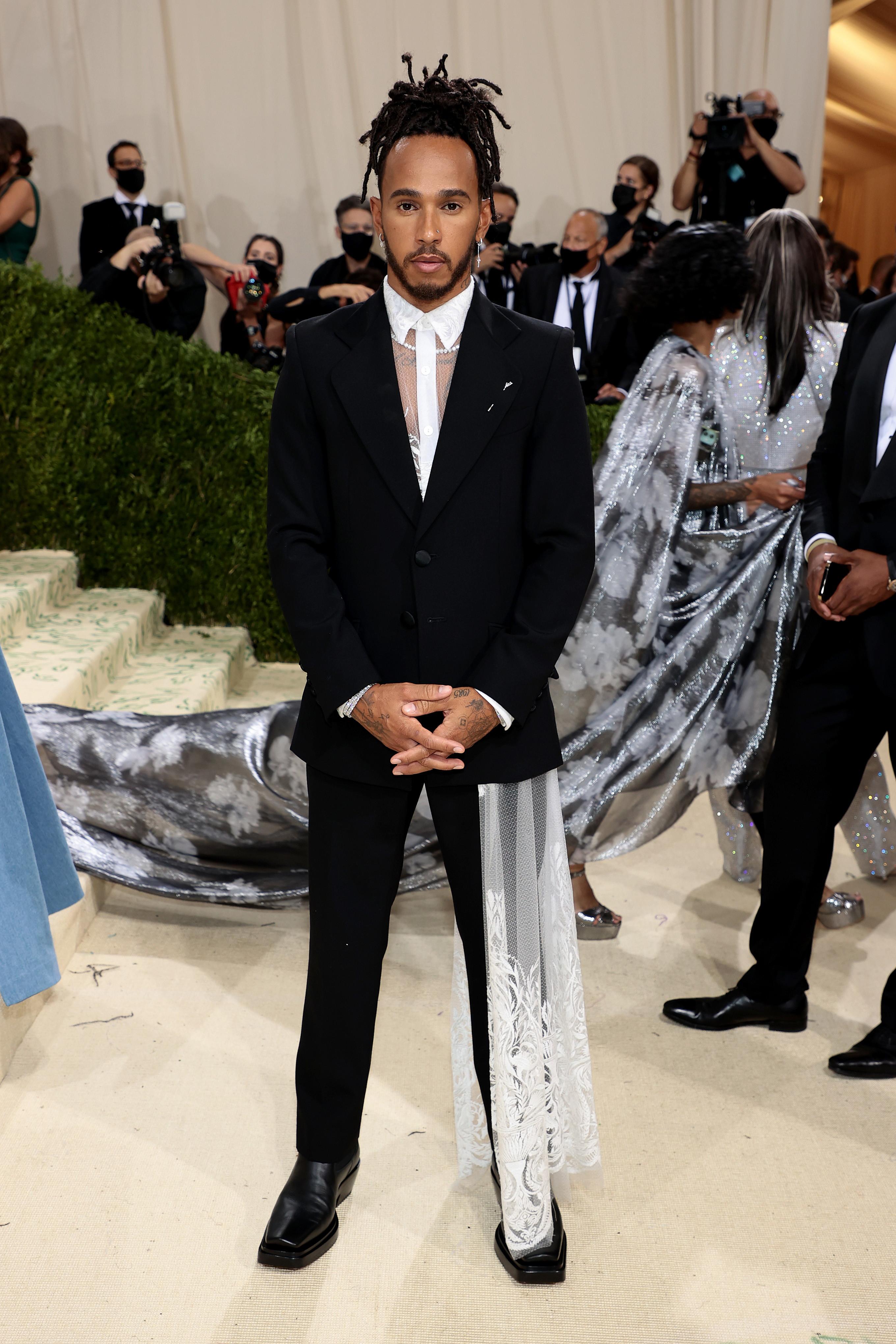 Look a dir poco stravagante per Lewis Hamilton sul red carpet del Met Gala 2021 a New York. Il pilota Mercedes ha indossato un abito e una camicia in pizzo di Kenneth Nicholson.&nbsp;<br /><br />